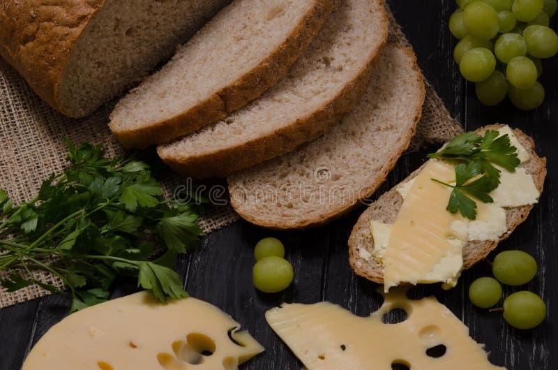 Αγροτικό τεμαχισμένο πρόγευμα ψωμί, τυρί, μαϊντανός, σάντουιτς και gre στοκ φωτογραφία με δικαίωμα ελεύθερης χρήσης