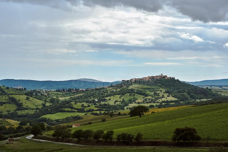 Αγροτικό τοπίο με τα κτήρια της πόλης σε έναν λόφο στοκ φωτογραφίες