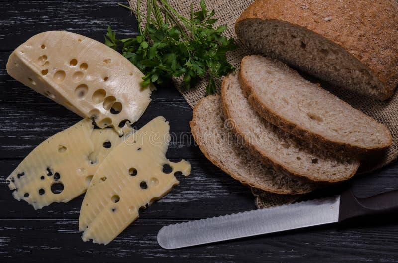 Αγροτικό τυρί, ψωμί, μαϊντανός και μαχαίρι προγευμάτων στο μαύρο W στοκ φωτογραφία με δικαίωμα ελεύθερης χρήσης