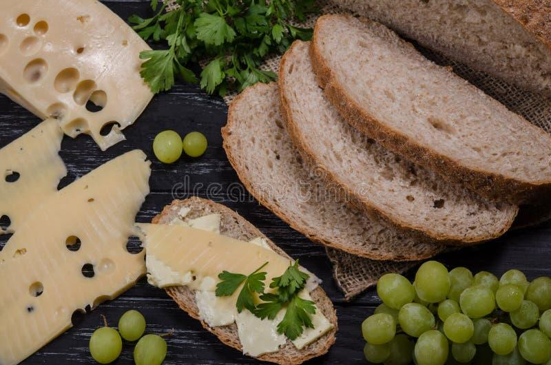 Αγροτικό τυρί, ψωμί, μαϊντανός και σταφύλι προγευμάτων στο μαύρο W στοκ εικόνες