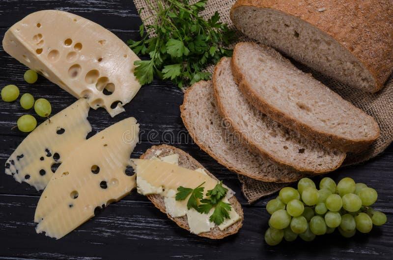 Αγροτικό τυρί, ψωμί, μαϊντανός και σταφύλι προγευμάτων στο μαύρο W στοκ φωτογραφία