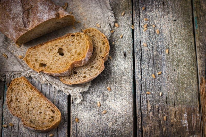 Αγροτικό υπόβαθρο τροφίμων με το φρέσκο σπιτικό ολόκληρο ψωμί σίτου στοκ φωτογραφία