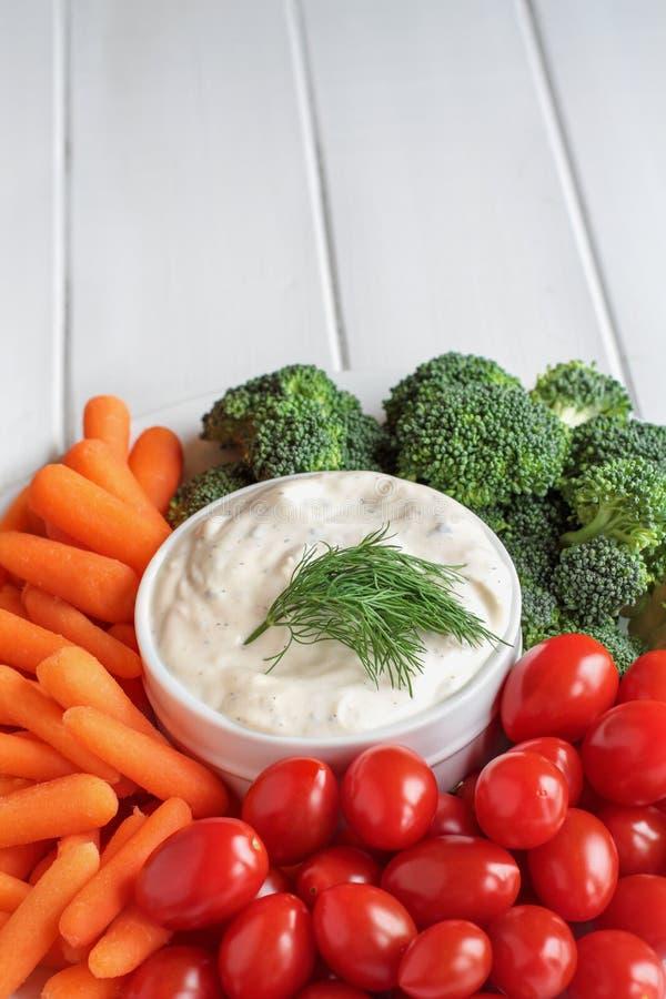 Αγρόκτημα που ντύνει με τον άνηθο και τα φρέσκα λαχανικά πέρα από τον άσπρο πίνακα στοκ εικόνα