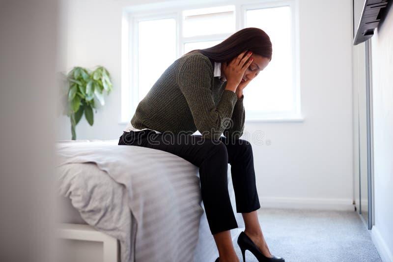 Αγχωμένη Επιχειρηματίας Με Κεφάλι Στα Χέρια Στην Άκρη Του Κρεβατιού Στο Σπίτι στοκ φωτογραφία