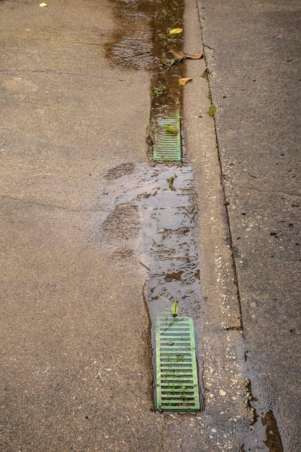 Αγωγός στη χαμηλή περιοχή συγκεκριμένο driveway με πράσινο σχάρα-που σταματούν επάνω με τη χλόη και το ρύπο με το μόνιμο νερό στοκ εικόνες