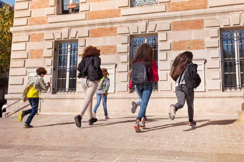 Αγόρια και κορίτσια με τα σακίδια πλάτης που τρέχουν στο κολλέγιο στοκ εικόνα