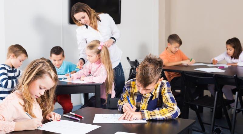 Αγόρια και κορίτσια με το σχέδιο δασκάλων στοκ φωτογραφία με δικαίωμα ελεύθερης χρήσης