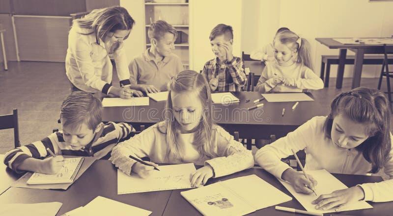 Αγόρια και κορίτσια με το σχέδιο δασκάλων στοκ εικόνες