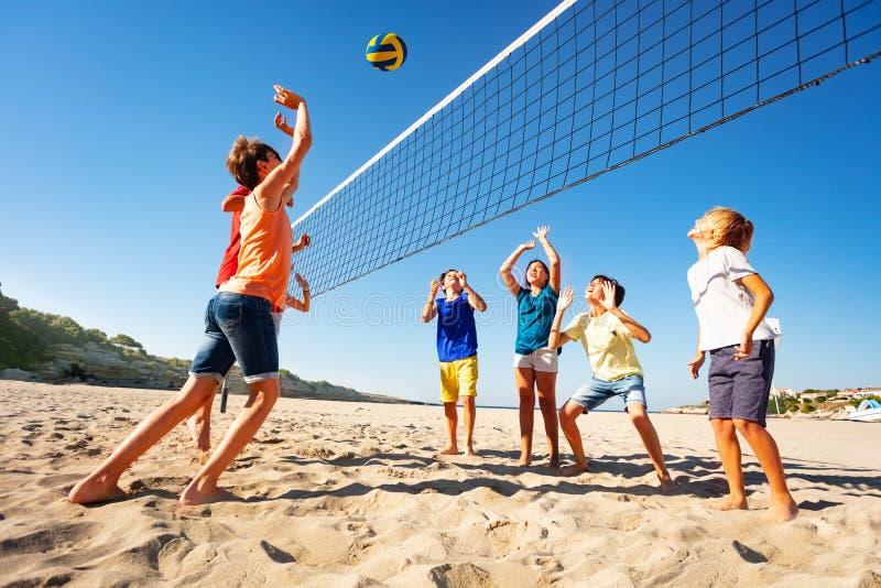 Αγόρια και κορίτσια που παίζουν την πετοσφαίριση στην παραλία στοκ εικόνες