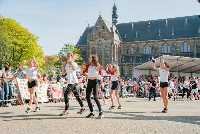 Αγόρια και κορίτσια που χορεύουν στην όμορφη και ζωηρόχρωμη παράγραφο λουλουδιών στοκ φωτογραφίες
