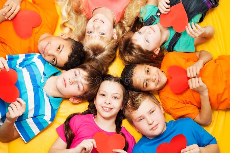 Αγόρια και κορίτσια στον κύκλο με τις καρδιές στοκ εικόνες