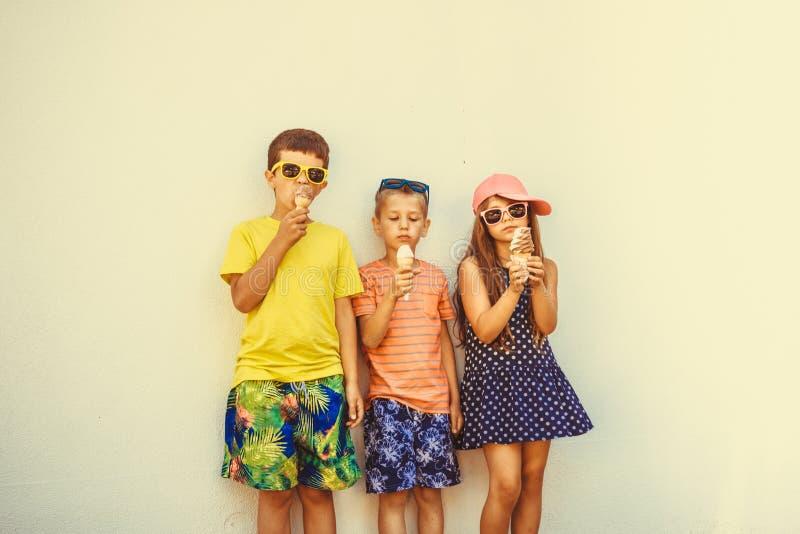 Αγόρια και μικρό κορίτσι παιδιών που τρώνε το παγωτό στοκ φωτογραφία