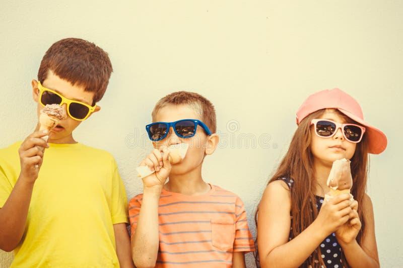 Αγόρια και μικρό κορίτσι παιδιών που τρώνε το παγωτό στοκ φωτογραφίες με δικαίωμα ελεύθερης χρήσης