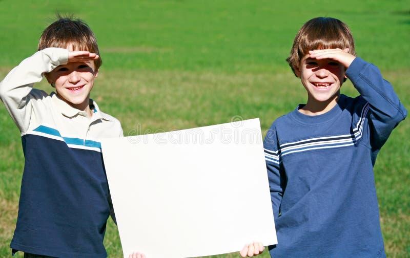 αγόρια που κρατούν το σημά&d στοκ φωτογραφία