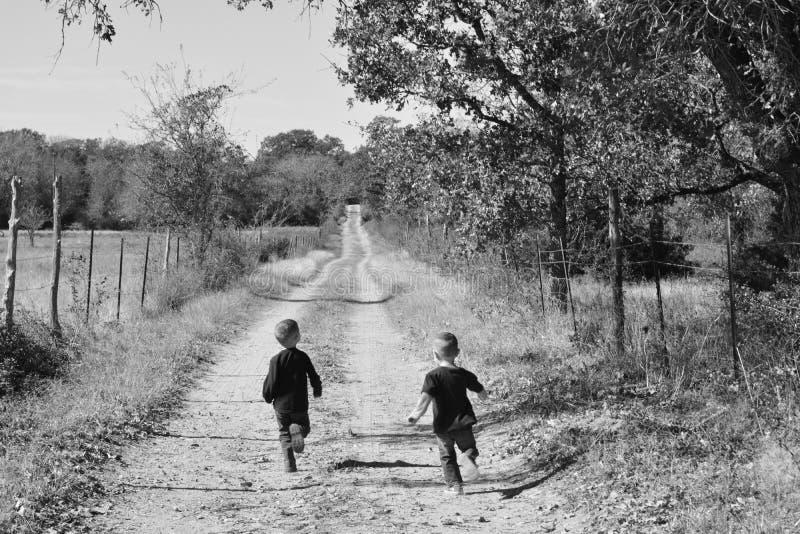 Αγόρια που μειώνουν έναν αγροτικό δρόμο χωρών στο αγρόκτημα στοκ εικόνα