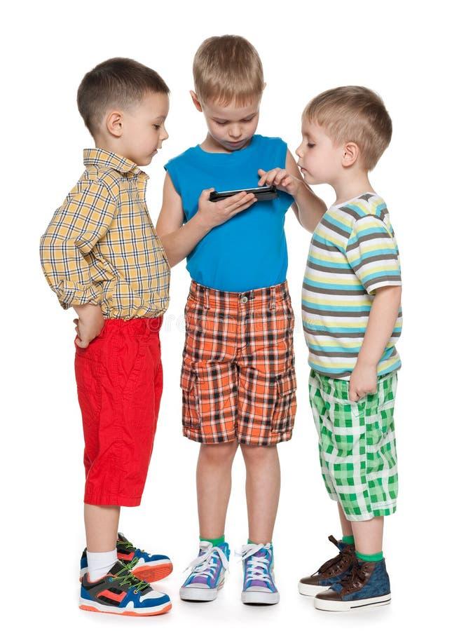 Αγόρια που με μια νέα συσκευή στοκ φωτογραφίες