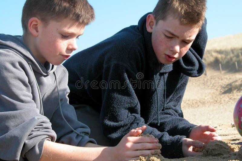Αγόρια που παίζουν στην παραλία στοκ εικόνα με δικαίωμα ελεύθερης χρήσης