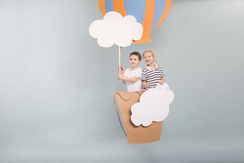 Αγόρια που πετούν στο baloon στοκ εικόνες