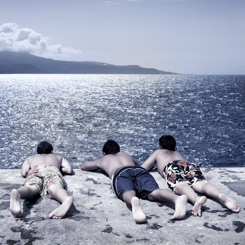 αγόρια που φαίνονται θάλασσα στοκ φωτογραφίες
