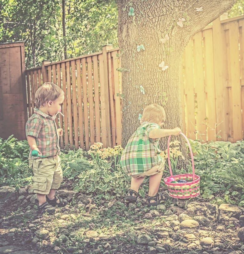 Αγόρια που ψάχνουν τα αυγά Πάσχας - αναδρομικά στοκ εικόνα