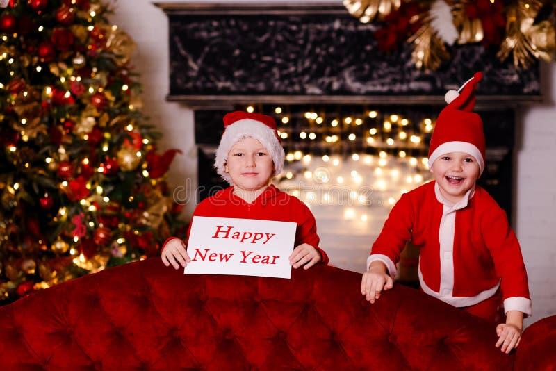 Αγόρια στα κόκκινα καλύμματα Santa που κρατούν ένα σημάδι στοκ εικόνες