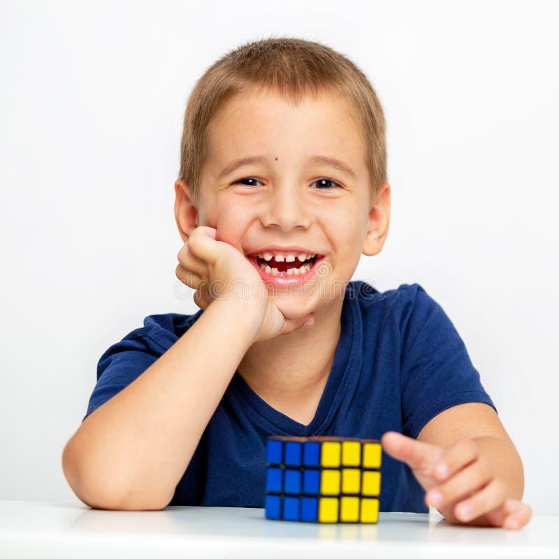 αγόρι έξυπνο Το παιδί έλυσε το πρόβλημα Συνέλεξε έναν κύβο Rubik ` s στοκ φωτογραφίες