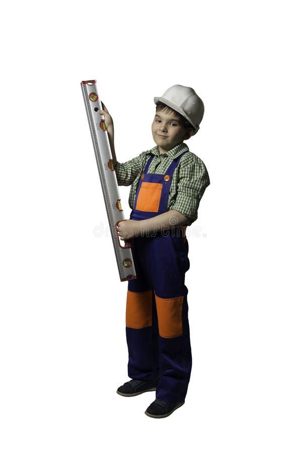 Αγόρι, έφηβος με τα εργαλεία για την επισκευή και κατασκευή, στις φόρμες και το κράνος, που απομονώνονται στοκ εικόνα