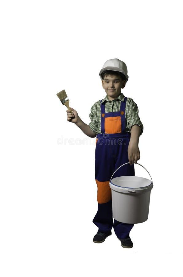 Αγόρι, έφηβος με τα εργαλεία για την επισκευή και κατασκευή, στις φόρμες και το κράνος, που απομονώνονται στοκ εικόνες