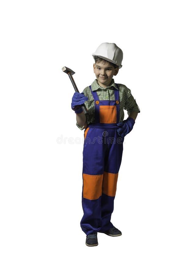 Αγόρι, έφηβος με τα εργαλεία για την επισκευή και κατασκευή, στις φόρμες και το κράνος, που απομονώνονται στοκ φωτογραφίες