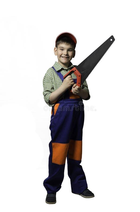 Αγόρι, έφηβος με τα εργαλεία για την επισκευή και κατασκευή, στις φόρμες και το κράνος, που απομονώνονται στοκ φωτογραφία