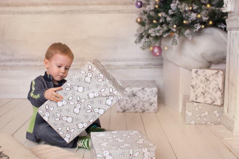 Αγόρι, ατμόσφαιρα Χριστουγέννων στο σπίτι, χριστουγεννιάτικο δέντρο στοκ εικόνα