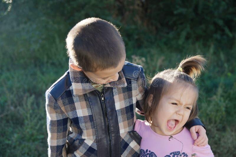 Αγόρι και αστείο μικρό κορίτσι που αγκαλιάζουν το πορτρέτο Ευτυχή χαμογελώντας παιδιά υπαίθρια στην ηλιόλουστη ημέρα Αμφιθαλείς φ στοκ εικόνα