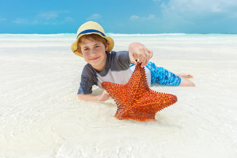 Αγόρι και αστερίας σε μια τροπική παραλία στοκ εικόνες