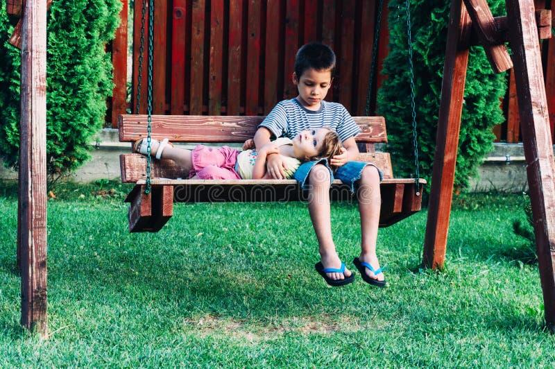 Αγόρι και η αδελφή του σε μια ταλάντευση στοκ φωτογραφία