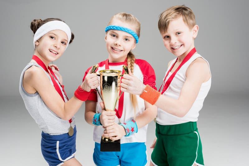 Αγόρι και κορίτσια με τα μετάλλια και goblet πρωτοπόρων στο γκρι στοκ εικόνες