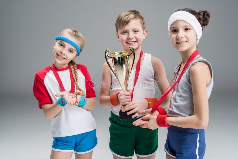 Αγόρι και κορίτσια με τα μετάλλια και goblet πρωτοπόρων στο γκρι στοκ φωτογραφία με δικαίωμα ελεύθερης χρήσης