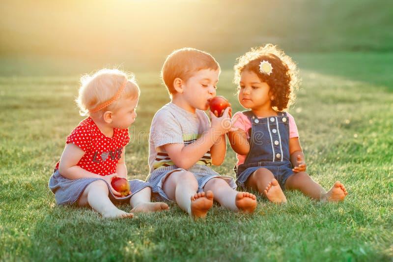 Αγόρι και κορίτσια παιδιών που κάθονται μαζί να μοιραστεί και που τρώνε τα τρόφιμα μήλων στοκ εικόνες