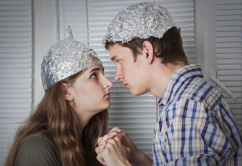 Αγόρι και κορίτσι ζευγών Teens στα καπέλα φιαγμένα από φύλλο αλουμινίου αργιλίου, protec στοκ φωτογραφίες
