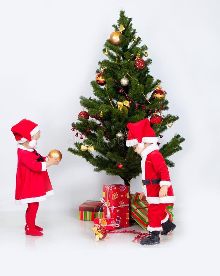Αγόρι και κορίτσι κοντά στο πεύκο Χριστουγέννων στοκ φωτογραφία με δικαίωμα ελεύθερης χρήσης