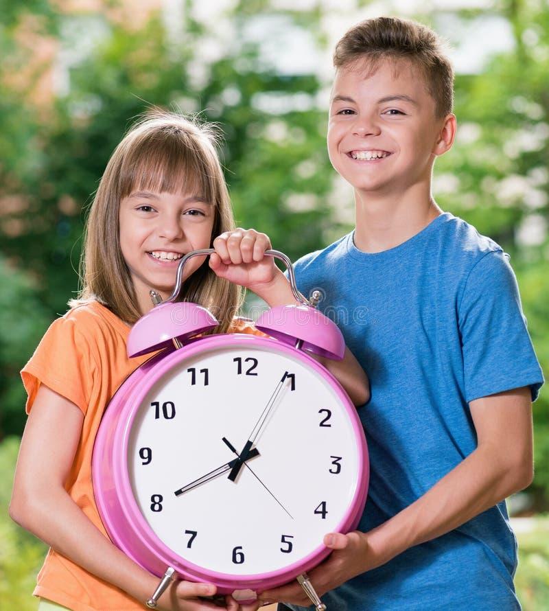 Αγόρι και κορίτσι με το μεγάλο ρολόι στοκ φωτογραφία με δικαίωμα ελεύθερης χρήσης
