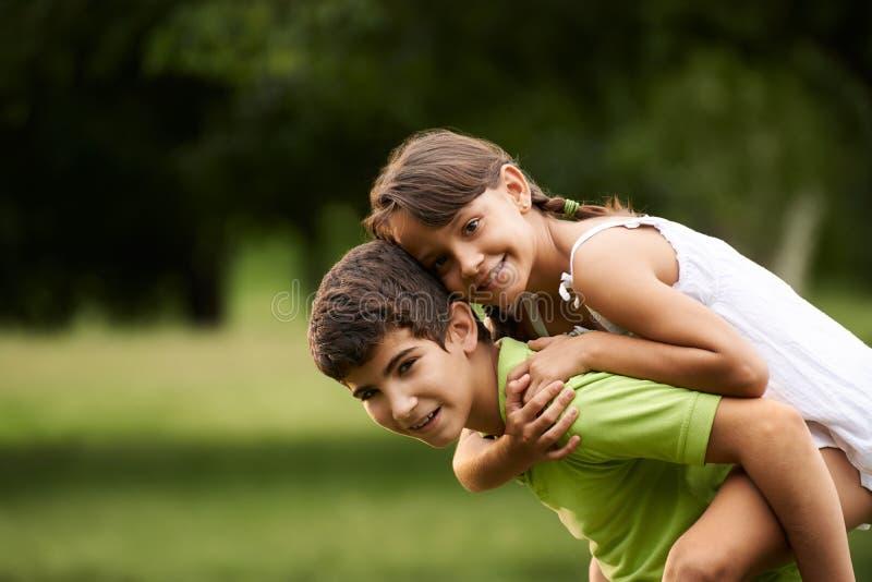 Αγόρι και κορίτσι παιδιών ερωτευμένα τρέχοντας piggyback το πάρκο στοκ φωτογραφίες
