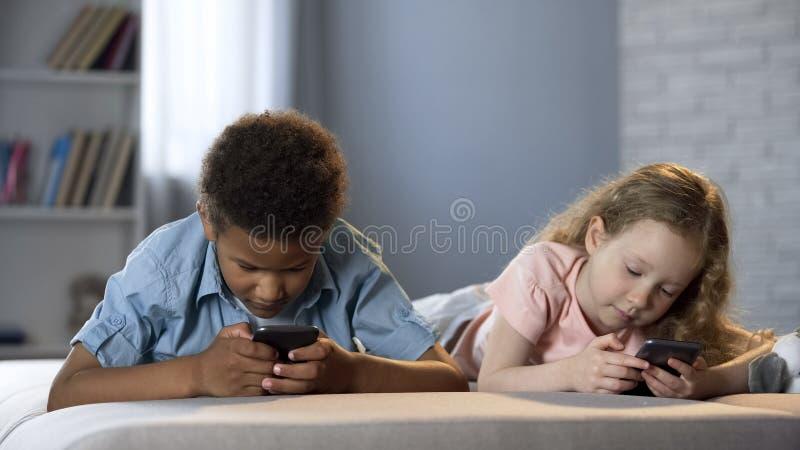 Αγόρι και κορίτσι που κάνουν σερφ Διαδίκτυο smartphones, έλλειψη επικοινωνίας, ψυχαγωγία στοκ εικόνα με δικαίωμα ελεύθερης χρήσης