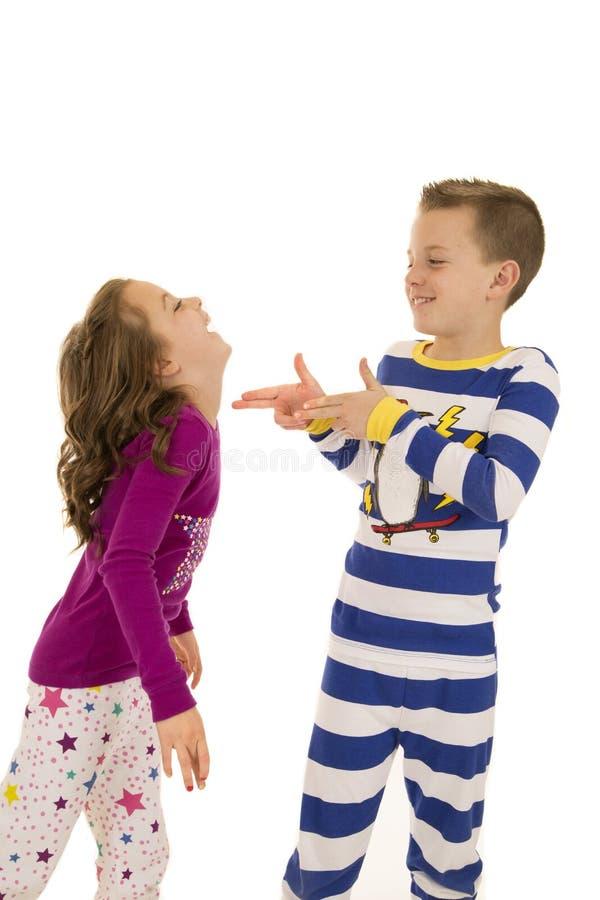 Αγόρι και κορίτσι που φορούν το παιχνίδι χειμερινών πυτζαμών ευτυχές στοκ φωτογραφίες με δικαίωμα ελεύθερης χρήσης