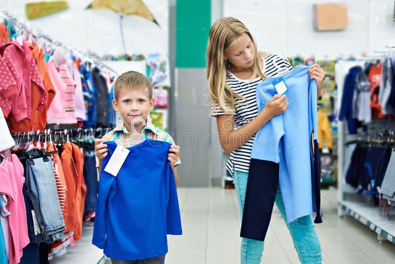 Αγόρι και κορίτσι στο κατάστημα ιματισμού στοκ εικόνες