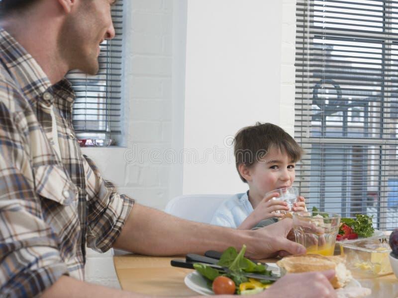 Αγόρι και πατέρας που έχουν το γεύμα να δειπνήσει στον πίνακα στοκ φωτογραφία