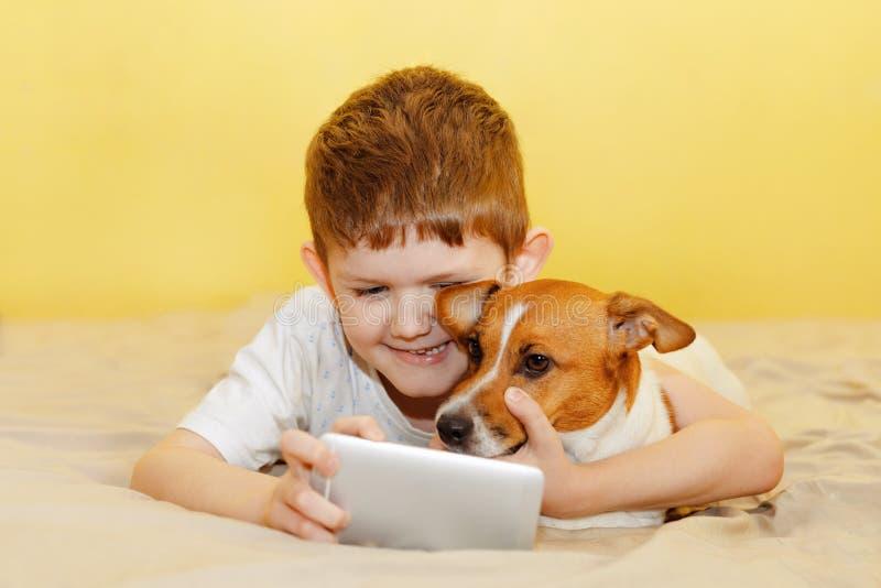 αγόρι και το παιχνίδι σκυλιών φίλων του στο smartphone στοκ φωτογραφίες