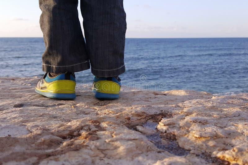 Αγόρι κινηματογραφήσεων σε πρώτο πλάνο ποδιών, ακτή της απεριόριστης θάλασσας στοκ εικόνα