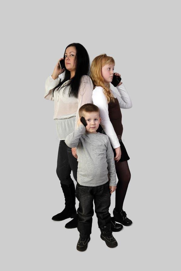 Αγόρι, κορίτσι και ενήλικη γυναίκα με τα smartphones στοκ εικόνες