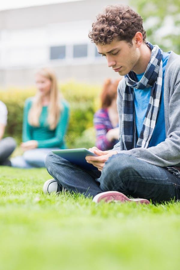 Αγόρι κολλεγίου που χρησιμοποιεί το επιτραπέζιο PC με τους θολωμένους σπουδαστές στο πάρκο στοκ φωτογραφία με δικαίωμα ελεύθερης χρήσης