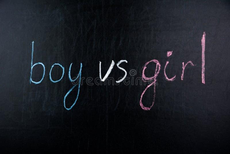 Αγόρι λέξεων εναντίον του κοριτσιού που γράφεται στον πίνακα κιμωλίας στοκ φωτογραφία με δικαίωμα ελεύθερης χρήσης